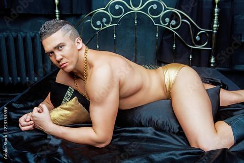 Fényképezés  muscular man   in bed with black linen