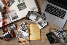 Old Family Photos On Wooden Background. Vintage Pictures, Camera, Notepad And Modern Notebook. Flat Lay.