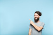 Leinwanddruck Bild young man pointing left and above his head to a virtual object or text. copy space for advertisement or product placement. portrait of a bearded hipster guy on blue background.