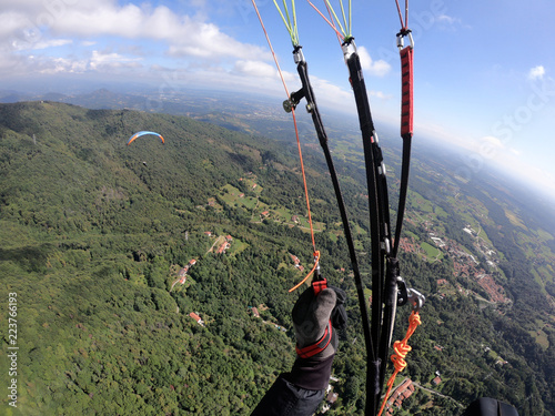 paragliding through the clouds in a beautiful summer day