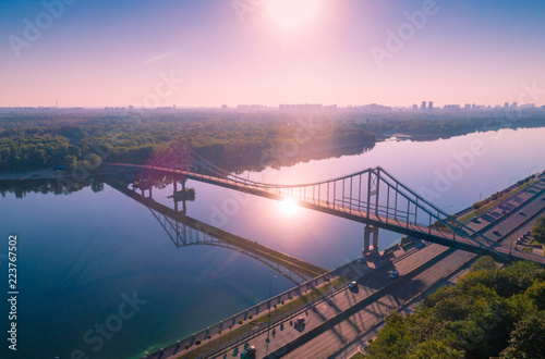 City of Kiev with a beautiful morning sky. Pedestrian bridge. The left bank of the Dnieper. Bird's-eye. Sunrise over the city
