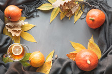 Fall Border And Still Life, Pumpkin, Dry Leaves, Gray Scarf For Cozy And Warming On Grey Board. Top View And Copy Space.