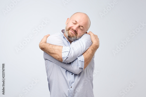 Fototapeta Closeup portrait of confident smiling man holding hugging himself isolated on grey wall background