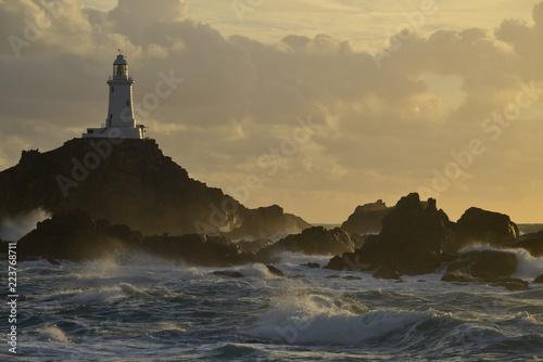 Foto op Aluminium Vuurtoren La Corbiere lighthouse, Jersey, U.K. A storm from the Atlantic lands at of coastal landmark in Autumn.
