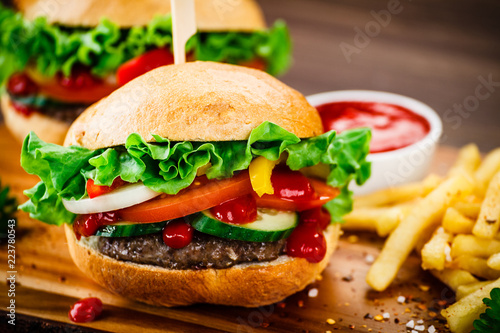 Tasty hamburgers with french fries served on fashionable black stone plate