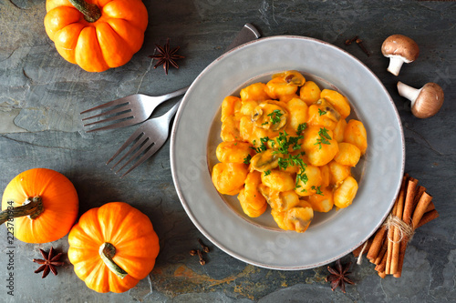 Gnocchi with a pumpkin, mushroom cream sauce. Autumn meal. Top view scene on a dark background.