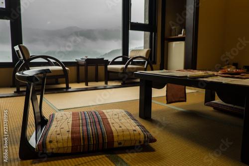 Fotodibond 3D Tradycyjny pokój w ryokanie - japoński hotel, z niskimi krzesłami i stolikami z przodu obrazu i oknem w tle. Mgliste góry to widok z okna.