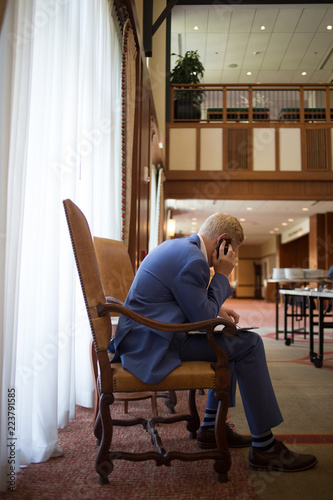 Fotografie, Obraz  Professional Caucasian Male - A man in a blue suit sitting in a chair talking on