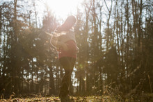Young Pregnant Woman In Last Trimester Standing In Autumn Forest