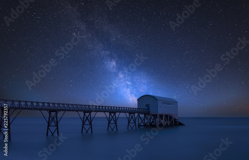 Foto op Aluminium Nachtblauw Vibrant Milky Way composite image over landscape of long exposure image of lifeboat jetty at sea