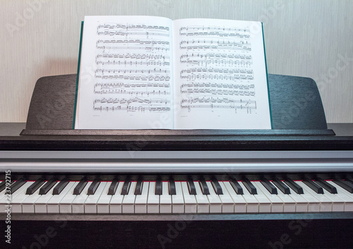 In de dag Muziekwinkel 2018.09.18, Moscow, Russia. An open book of sheet music on the piano. A composition of the sheet music and the piano keyboard. Elements of interior of the music classroom.