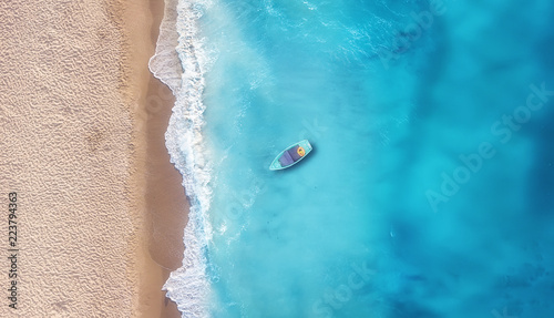 Boat on the water surface from top view. Turquoise water background from top view. Summer seascape from air. Travel concept and idea
