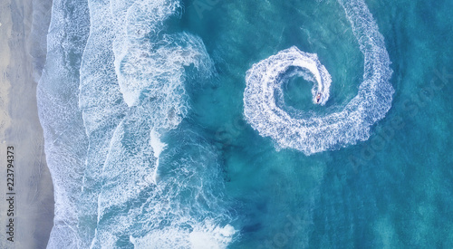 Scooter at the sea surface. Aerial view of luxury floating boat on transparent turquoise water at sunny day. Summer seascape from air. Top view from drone. Seascape with motorboat in bay.