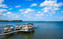 Boat Dock With Raised Pontoons On Beautiful Lake In Northern Minnesota With Blue Sky And Fluffy Clouds