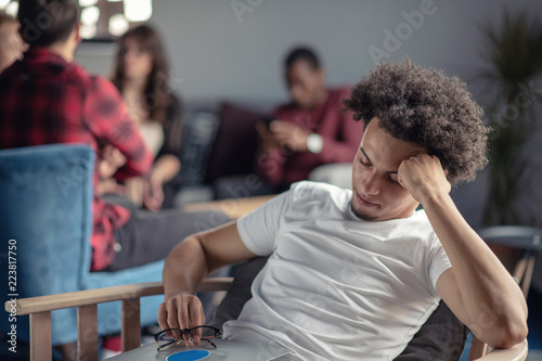 Fotografia  Worried Man with curly hair working on laptop.
