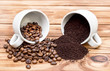 Coffee beans with ground coffee scattered from cups on the wooden table.