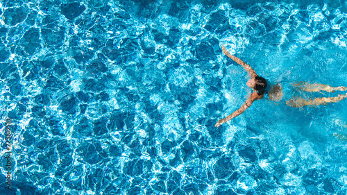 Fotografia Aerial drone view of active girl in swimming pool from above, yong woman swims i