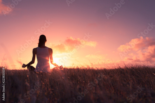 Young woman meditating outdoors at sunset.