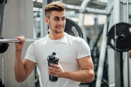 Fotografia Athlete man having a snack with protein cocktail in shaker over gym machine back