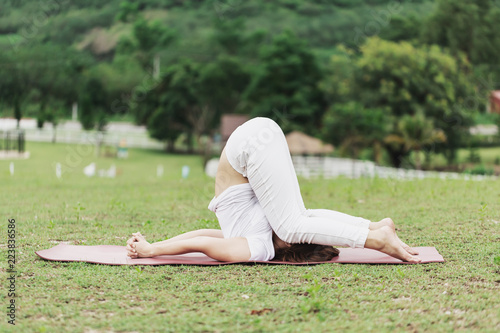 Beautiful Attractive Asian woman sitting on yoga mat practice Karnapidasana or Ear Pressure Pose with yoga meditation relax and refresh health on green grass feeling happiness and comfortable