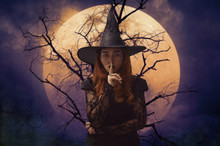 Halloween Witch Showing Silence Sign With Finger Over Lips Standing Over Dead Tree, Full Moon And Spooky Cloudy Sky, Halloween Mystery Concept