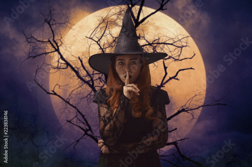 Fototapeta Halloween witch showing silence sign with finger over lips standing over dead tr