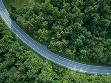 TOP DOWN: Cool Shot Of Long Curve Of Asphalt Road Running Through The Forest.