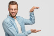 Leinwandbild Motiv Cheerful unshaven guy stands sideways, holds background, gestures with both hands as if carrying something, shows height of thing, dressed in fashionable clothes, isolated over white background