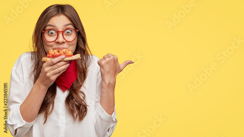 In de dag Kruidenierswinkel Lunch time concept. Attractive cheerful woman eats delicious Italian pizza, surprised with wonderful taste, indicates with thumb aside, shows where pizzeria situated, suggests to visit and have snack