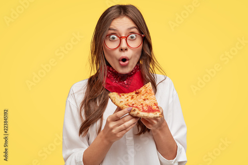 Shocked youngster has snack during dinner time, enjoys delicious pizza, being surprised with its low price, has unhealthy lifestyle, eats junk food, stands against yellow background. Eating concept