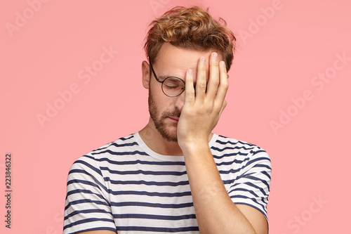 Fotografie, Obraz  Tired overworked curly ordinary man keeps hand on face, closes eyes, feels sleepy after working all night, dressed in striped t shirt, isoated over pink studio wall