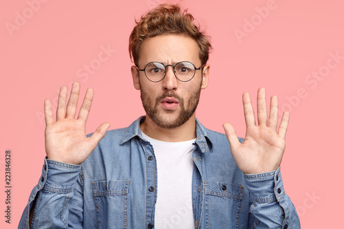 Slika na platnu Calm down, please! Handsome unshaven Caucasian man keeps palms in front, asks to