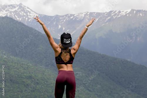 Fit female runner with long blond hair under baseball cap resting after jogging Wallpaper Mural