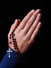 Female Hands Praying Holding A Beads Rosary With Jesus Christ In The Cross Or Crucifix On Black Background. Woman With Christian Catholic Religious Faith. Profile Or Side View