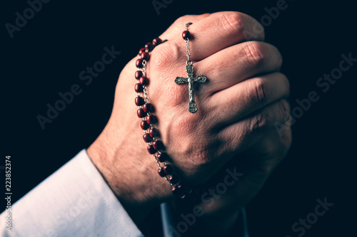 Fotografie, Obraz Male hands praying holding a rosary with Jesus Christ in the cross or Crucifix on black background