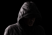 Scary And Creepy Caucasian Or White Man Hiding In The Shadows, With The Face And Identity Hidden With The Hood, And Standing In The Darkness. Low Key, Black Background. Concept For Fear, Danger,