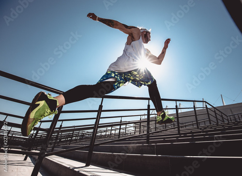 Foto auf AluDibond Jogging Handsome young muscular man in modern sport clothing run up the stairs outdoor at bright sunny day. Wide angle photo of a jogging man. Sport lifestyle