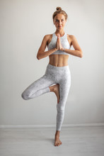Tan Skin Caucasian Woman Wearing White Elastic Sports Clothes Meditating In Yoga Tree Pose At Studio White Background. Healthy Lifestyle, Yoga Fitness Concept.