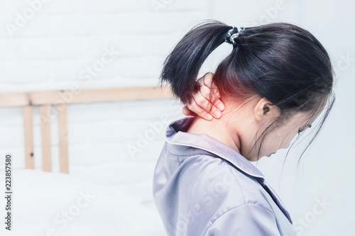 Asian woman back pain and sit on bed in bedroom in the morning.color tone