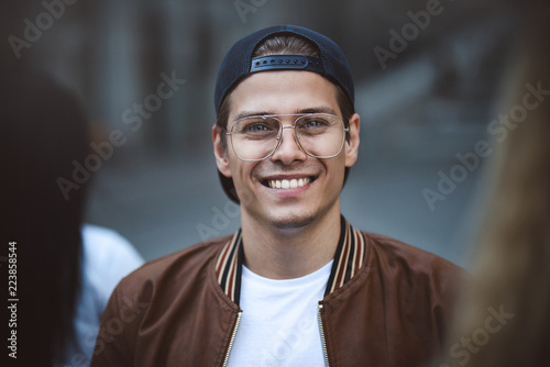 Young happy man posing on a crowded street