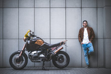 Handsome Rider Guy Standing Next To Classic Style Cafe Racer Motorcycle Near The Wall At Day Time.