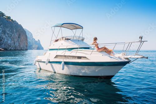 Piękna kobieta relaksuje się na prywatnym jachcie na morzu w pobliżu wysp.