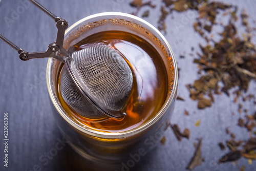 Fotografia, Obraz  Double walled glass with tea and stainless steel tea infuser