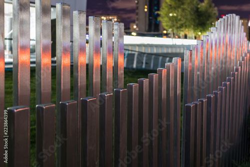 Fotografia  The wavy wood fence near the road in the colours of car traffic lights