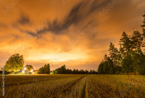 long exposure night photo of forest, harvested field and dark heavy clouds at swedish country side