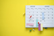 canvas print picture - close up of calendar on the yellow background, planning for business meeting or travel planning concept