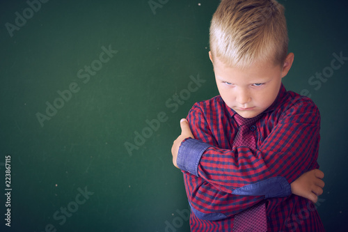 Concept of bullied school boy. Sad and angry little Caucasian boy is hugging himself with his hands standing on the background of the school board