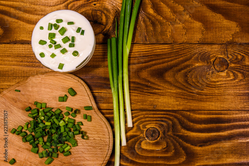 Foto op Plexiglas Fitness Glass bowl with sour cream and cutting board with chopped green onion on wooden table. Top view