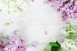 Fresh lilac flowers frame over white wooden background with copy space, flat lay floral composition