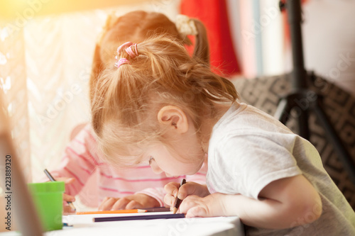 Fotografie, Obraz  Two little girls draw with colored pencils